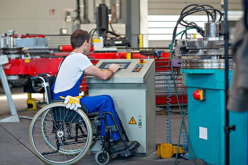 man on wheelchair working in machine shop